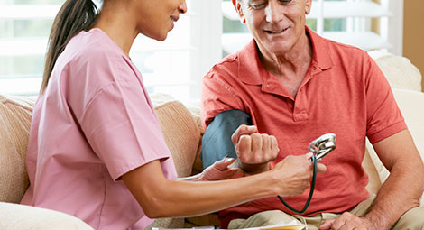Man getting blood pressure checked by nurse at home